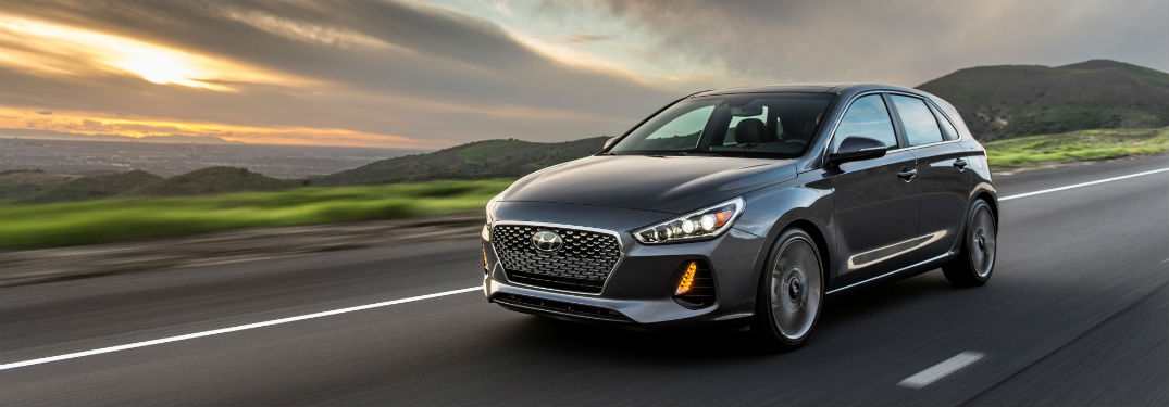 Silver 2018 Hyundai Elantra GT driving down the road with a sunset in the background