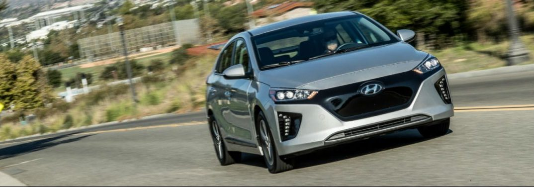 Silver 2019 Hyundai Ioniq drives through sunny hills flecked with buildings.
