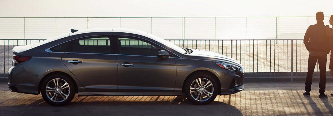 Grey Hyundai Sonata exterior side-view on a boardwalk at sunset.
