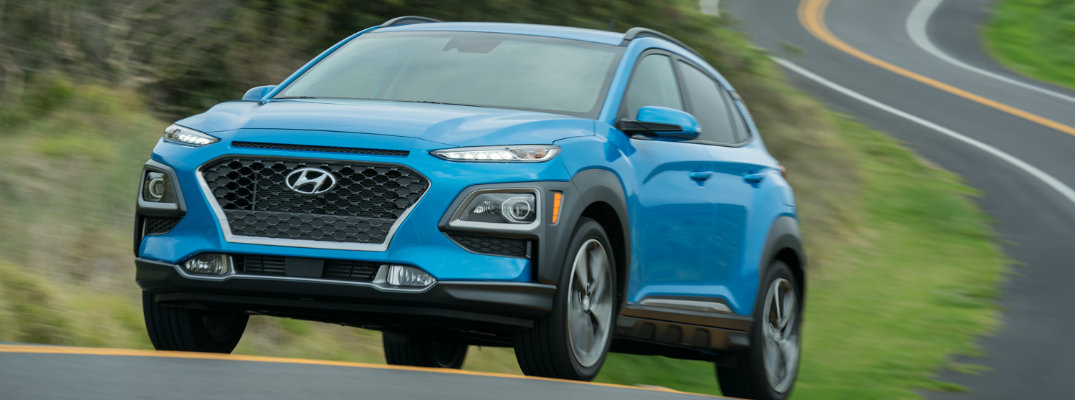 2019 Hyundai Kona exterior shot with surf blue paint color driving on a twisting country road