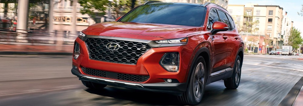 Front view of red 2019 Hyundai Santa Fe driving on city road