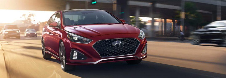 Red 2019 Hyundai Sonata driving on city road