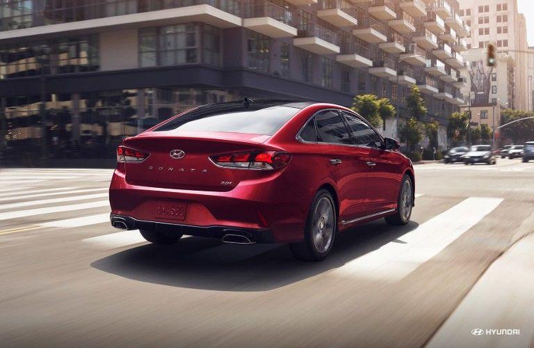 Rear view of red 2019 Hyundai Sonata driving in city