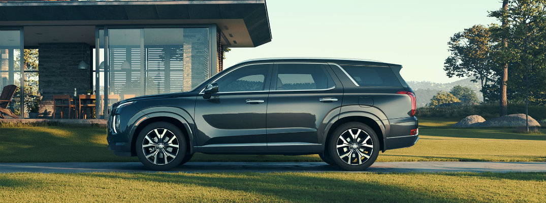 2020 Hyundai Palisade exterior side shot parked outside a luxury home on a concrete strip between grass