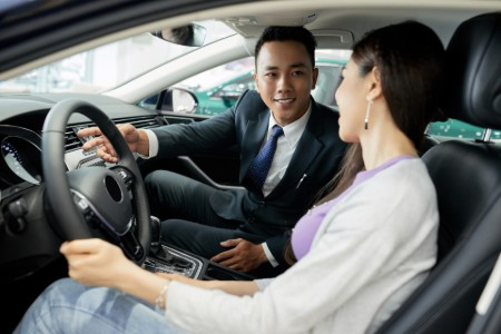 Dealer Showing a Car to a Buyer