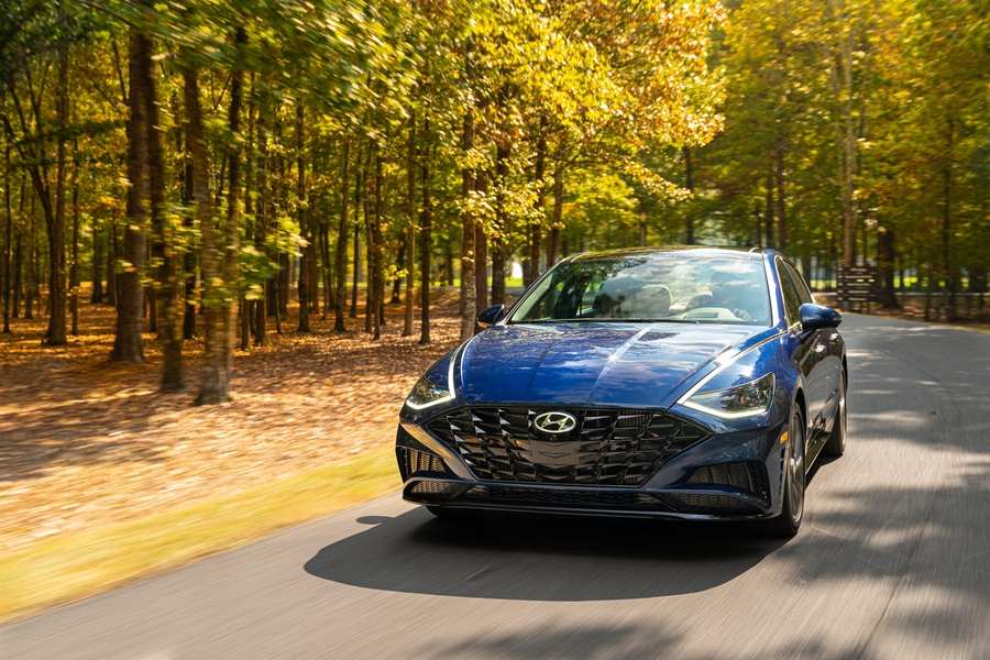 Blue 2020 Hyundai Sontana from front on road with fall trees in background