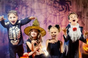Four kids dressed up for Halloween with pumpkins