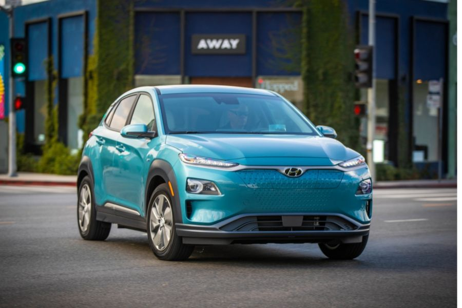 Teal 2020 Kona Electric in front of stores