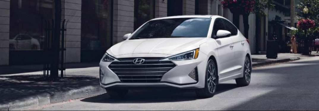 White 2020 Hyundai Elantra parked by a sidewalk.