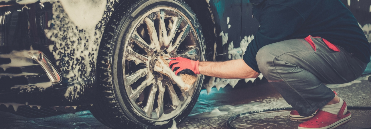 service worker washing and waxing wheels of car