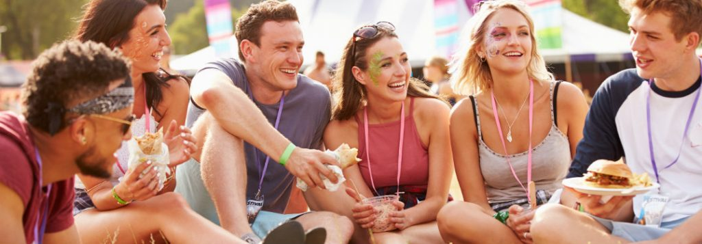 group of friends eating and drinking outdoors at festival