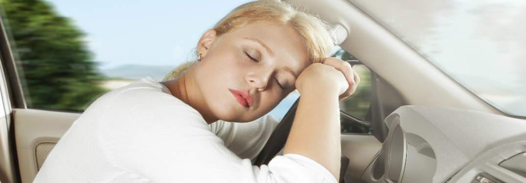 Woman rests head while sleeping in car