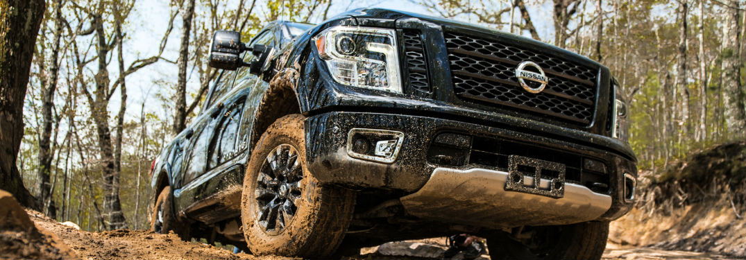 muddy 2019 Nissan TITAN driving through the forest