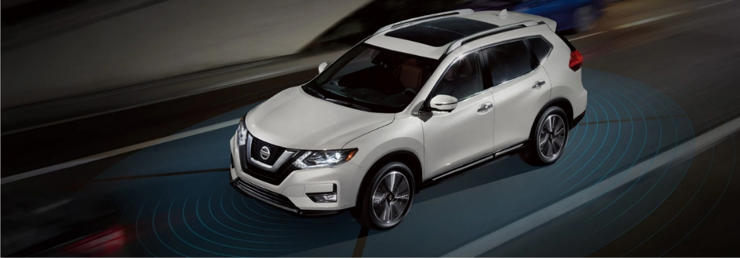 Graphic of White Nissan Rogue on a Highway with Nissan ProPILOT Assist Sensors Around the Vehicle