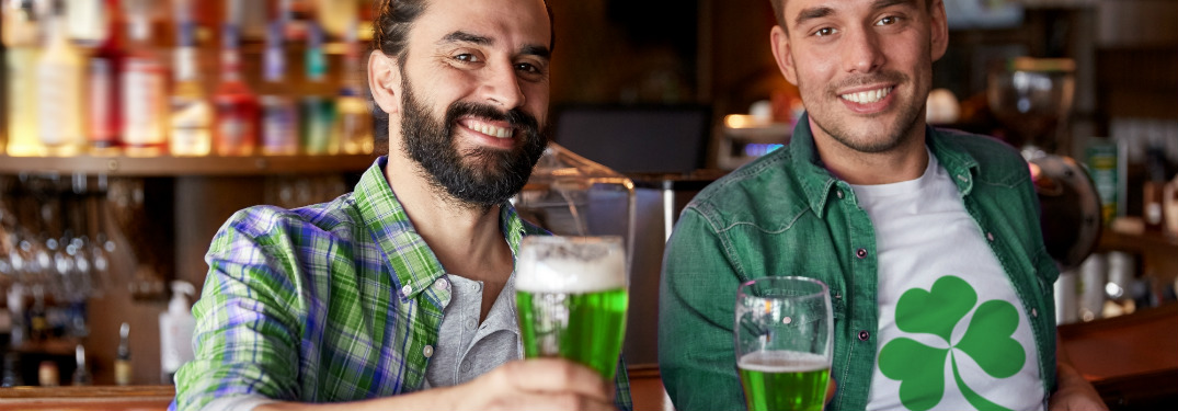 Two men hold green beers and wear green clothing with Irish symbols. They appear to be toasting the camera and smiling in a welcome manner.