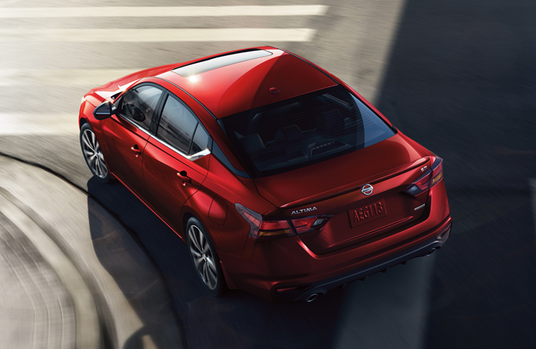 Red 2019 Nissan Altima cruises around a corner. Overhead angled view.