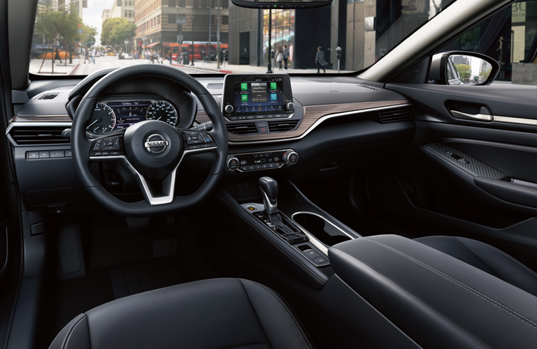 Interior front dashboard, infotainment, and steering wheel of a 2019 Nissan Altima.