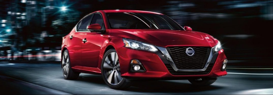 Red 2020 Nissan Altima cruises down a city street at night.