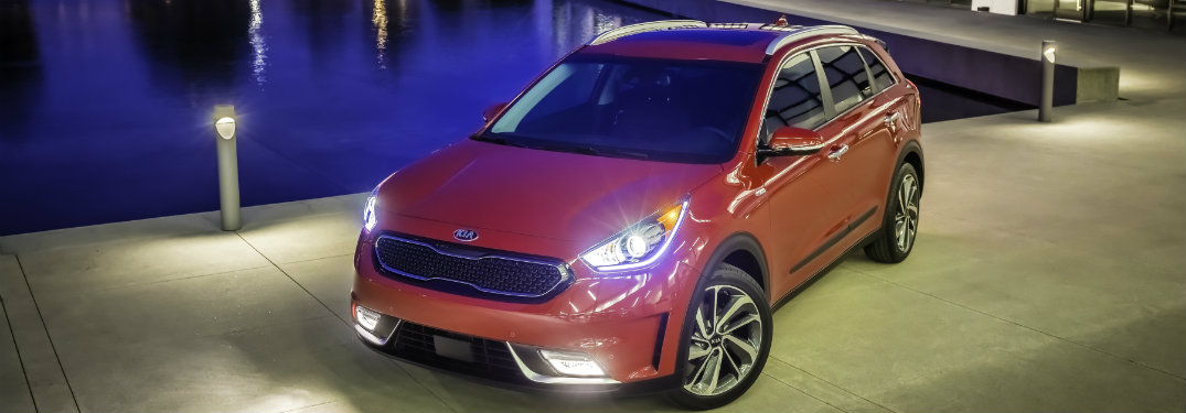 front view of red kia niro with headlights on