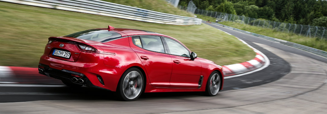 rear and side view of red kia stinger on race track