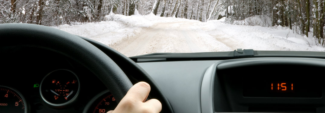 person holding steering wheel, driving on snowy road