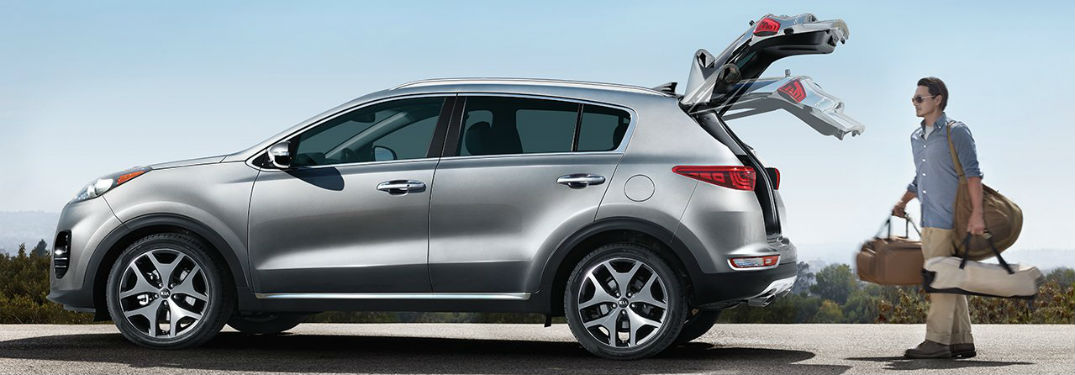 Driver side view of a gray 2019 Kia Sportage with a man utilizing the rear power lift gate to easily load luggage