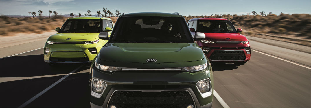 Front exterior view of a green 2020 Kia Soul flanked by a yellow and a red 2020 Kia Soul