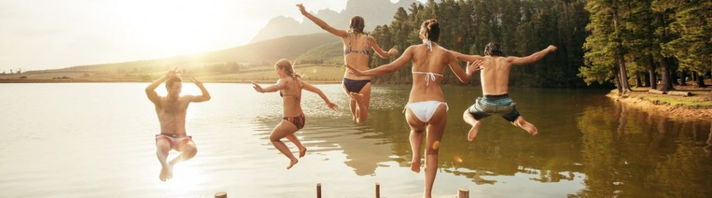 A family jumping into a large lake