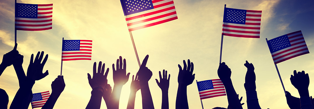 Hands Waving Small American Flags With Sun Shining In Background