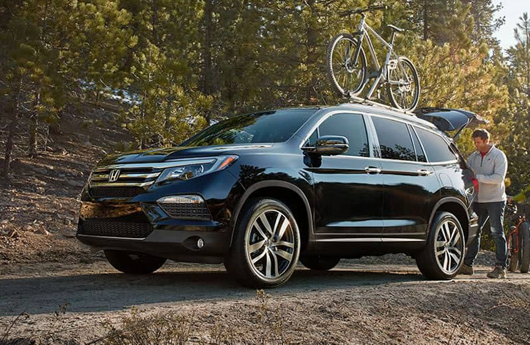 View of blue 2018 Honda Pilot parked on dirt road with bike on roof rack