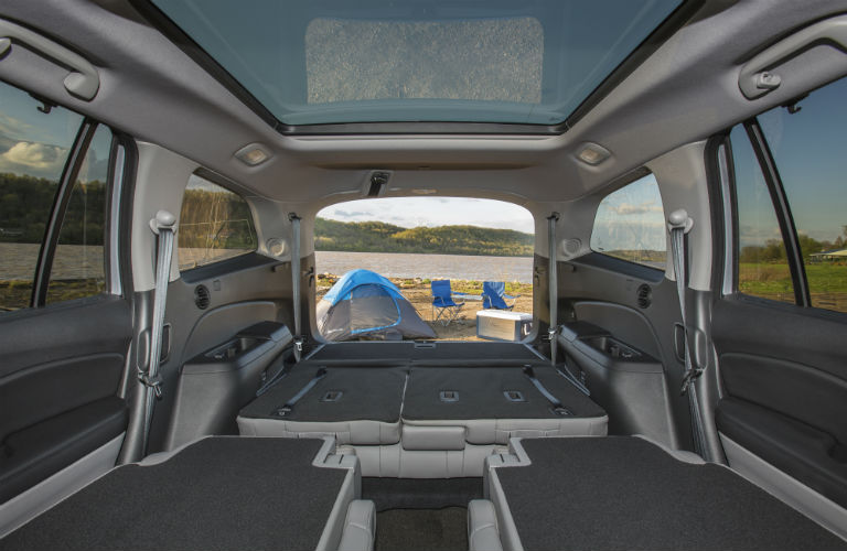 Interior view of 2018 Honda Pilot with all seats folded down and back hatch open to a camping tent by the beach