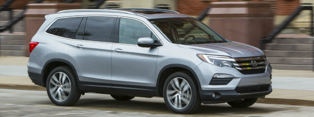 View of silver 2018 Honda Pilot driving down a city street during the day