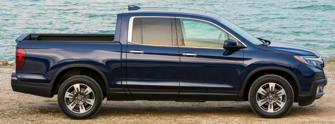 Side View of blue 2019 Honda Ridgeline parked in the sand with large body of water in background