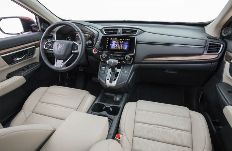 Interior view of a 2018 Honda CR-V showing beige seating and dashboard with steering wheel