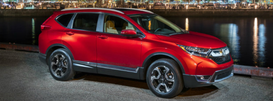 Exterior view of a red 2018 Honda CR-V parked next to a body of water at night