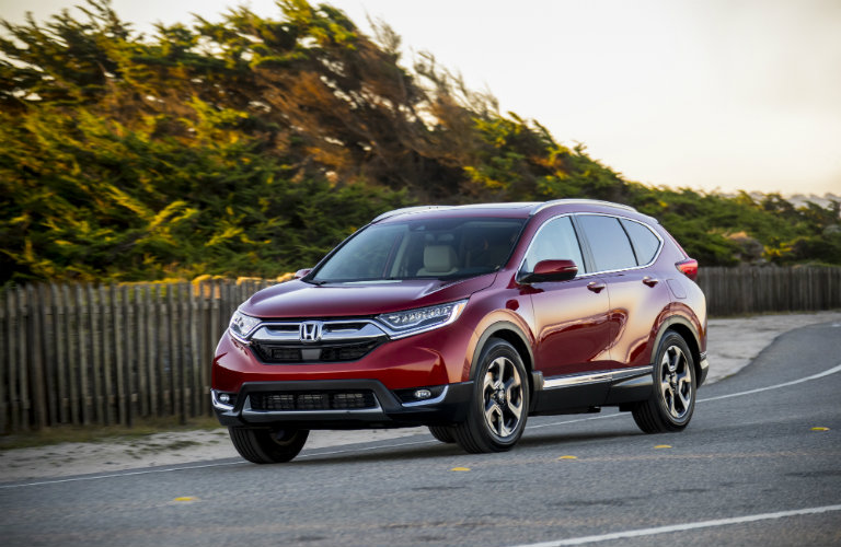 Exterior view of a red 2018 Honda CR-V parked on a street with trees in the background