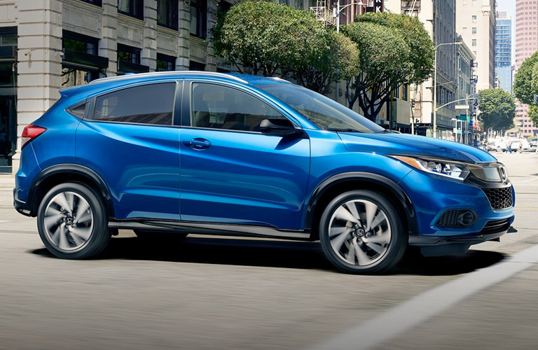 Exterior view of a blue 2019 Honda HR-V driving down a city street
