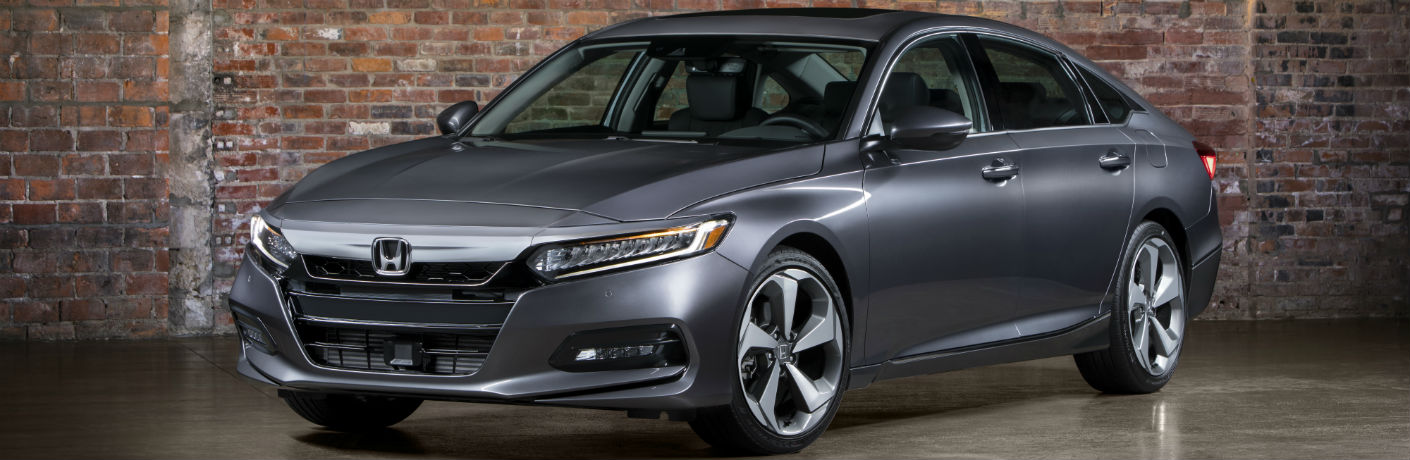 Exterior view of a gray 2018 Honda Accord parked in a showroom with brick background
