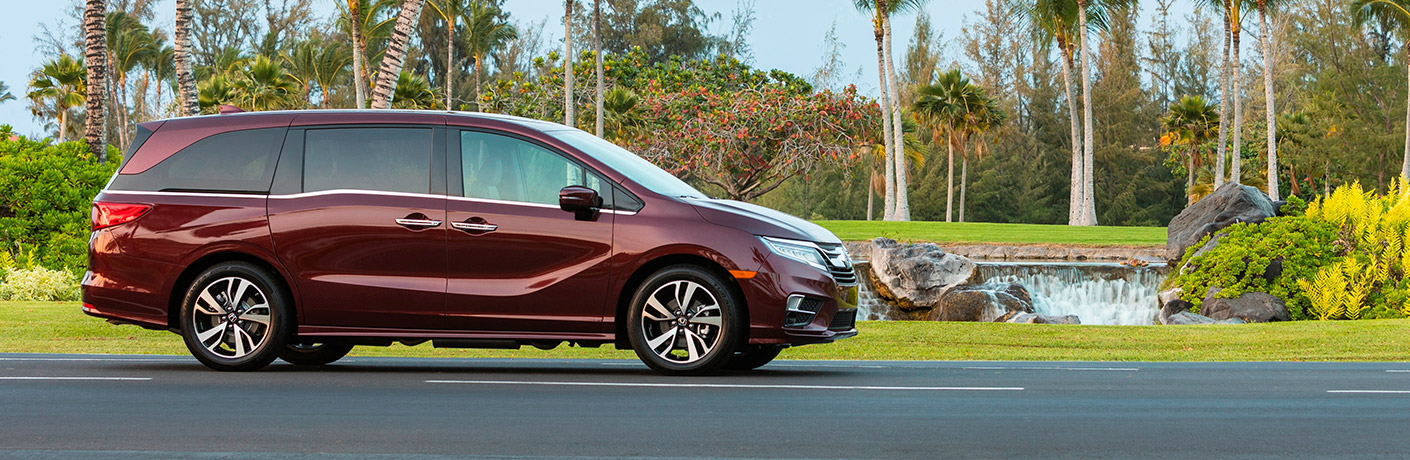 Exterior view of the passenger's side of a 2019 Honda Odyssey driving down a road past beautiful scenery