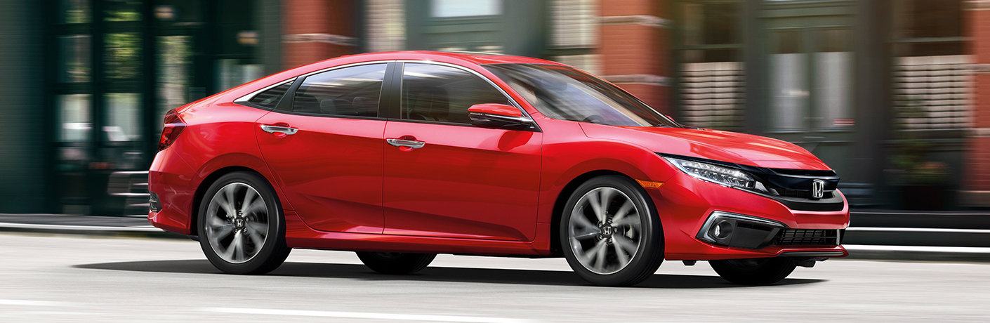 Exterior view of a red 2019 Honda Civic diving down a city street