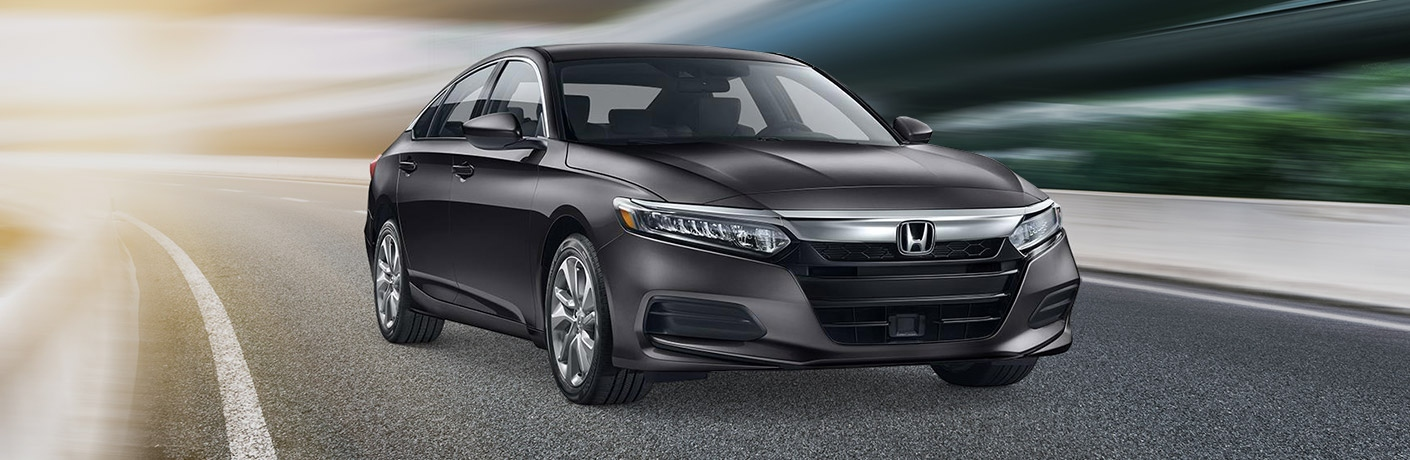 Exterior view of a black 2019 Honda Accord placed against a racetrack background