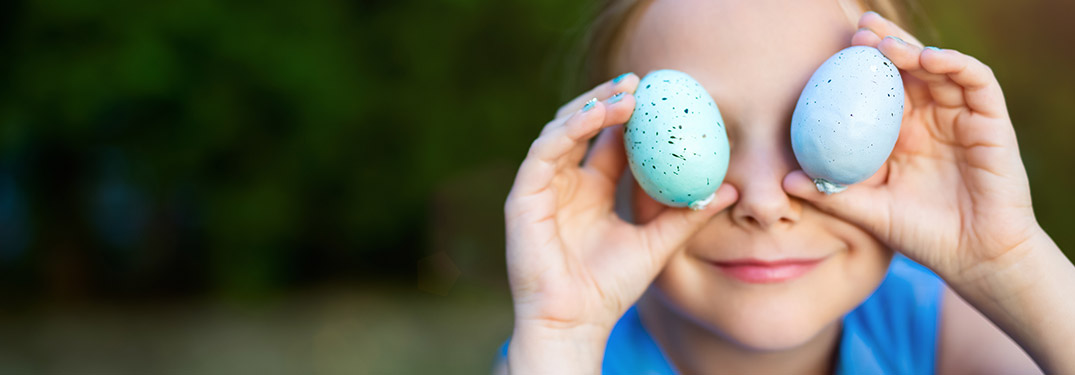 Image of a child holding two blue Easter Eggs in front of his eyes
