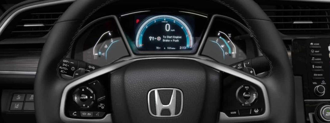 Closeup view of the steering wheel and dashboard inside a Honda vehicle
