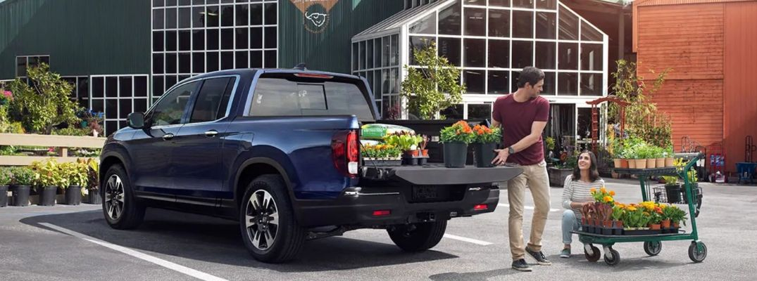 Exterior view of a blue 2019 Honda Ridgeline with a bed full of plants and gardening items