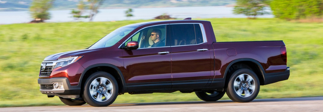 2020 Honda Ridgeline red driving to the left grass and lake in background