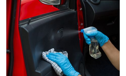 gloved hands cleaning inside of red car door