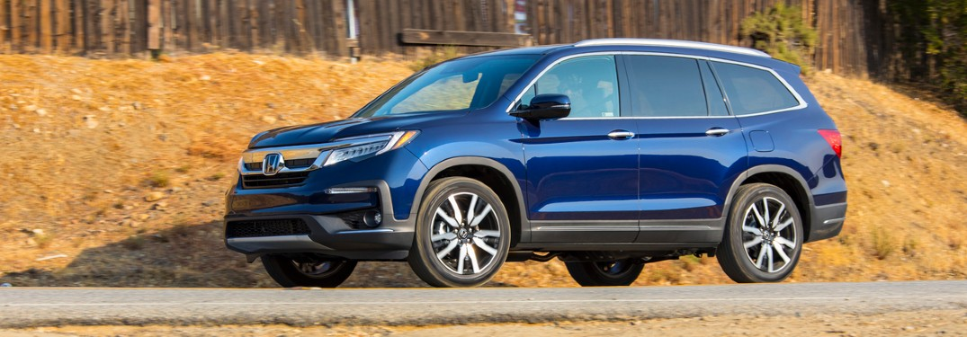 2021 Honda Pilot Elite 2019 shown blue parked in front of hill with wood fence
