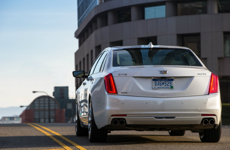 White cadillac ct6 driving down road, rear