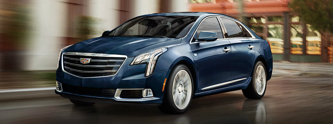 Blue 2018 Cadillac XTS model driving down city street with buildings and trees in background