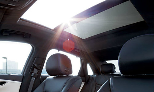 Seats of 2018 Cadillac XTS shown with sun shining through available sunroof